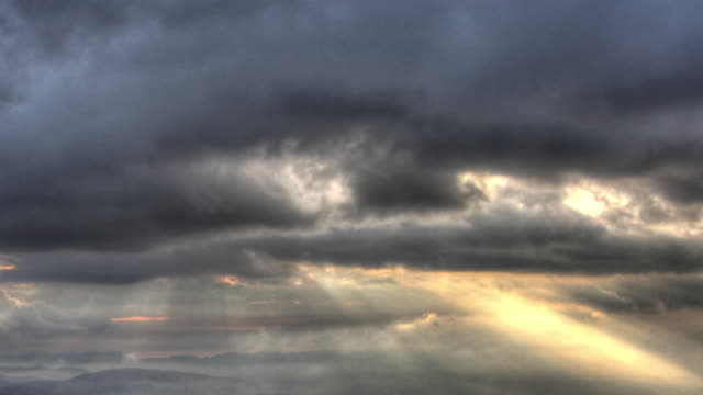 Time lapse shot of sun rays piercing through dark storm clouds.