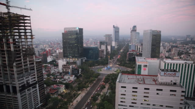 vídeos de stock, filmes e b-roll de time lapse shot of the bbva building under construction and the angel of independence monument as the city lights slowly fade as the day begins on a... - monumento da independência paseo de la reforma