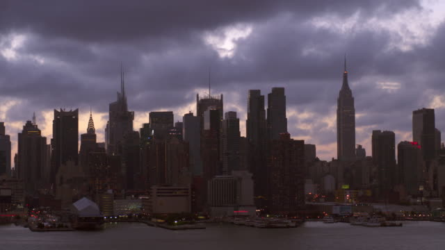 vídeos de stock e filmes b-roll de time lapse shot of the midtown manhattan skyline. clouds can be seen passing by at high speed. the empire state building, new york times building, and the chrysler building can all be seen - prédio chrysler