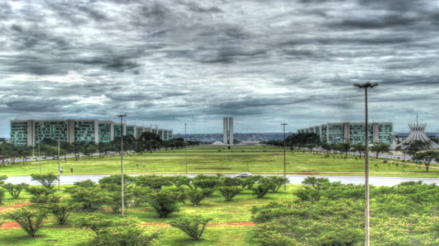 vídeos de stock, filmes e b-roll de time lapse shot of the national congress palace and government buildings on brasilia's monumental axis avenue. - high dynamic range imaging
