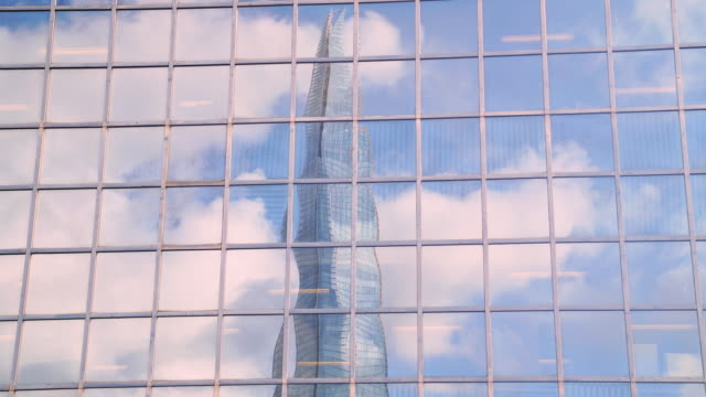 time lapse shot of the shard reflected in the windows of a nearby skyscraper. - skyscraper stock videos & royalty-free footage