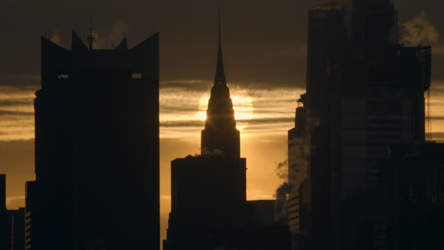 vídeos de stock e filmes b-roll de time lapse shot of the sun rising over the chrysler building on the  manhattan skyline in new york city. the sky is lit up a warm yellow. the sun rises through the passing clouds - prédio chrysler