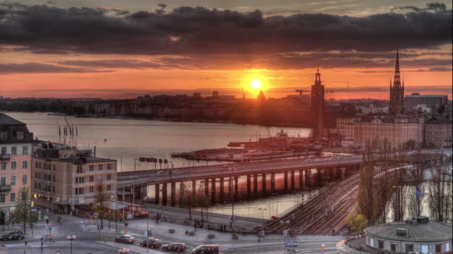 vidéos et rushes de time lapse shot of the sun setting over the city of stockholm. - transport