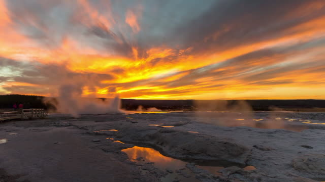 time lapse shot of tourists by hot spring emitting smoke against orange cloudy sky during sunset - yellowstone national park, wyoming - emitting stock videos & royalty-free footage