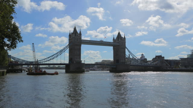 time lapse shot of tower bridge over river in city against sky during sunny day - london, united kingdom - 跳開橋点の映像素材/bロール