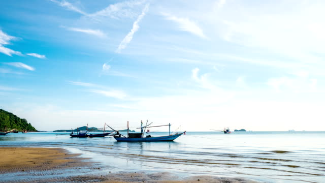 Time lapse shot of Traditional Fishing Boat on Beach with Blue Sky and Wave