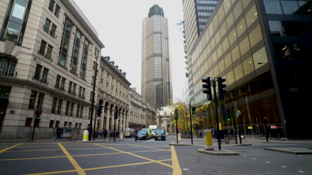 time lapse shot of traffic and pedestrians travelling near tower 42 in london. - stadtzentrum stock-videos und b-roll-filmmaterial