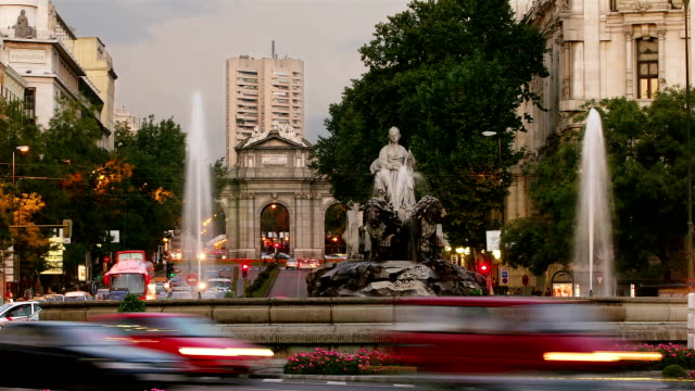 time lapse shot of traffic passing fountain of cibeles at junction of paseo del prado and calle de alcala with view of puerta de alcala / dusk to night / madrid, spain - paseo del prado madrid stock videos and b-roll footage