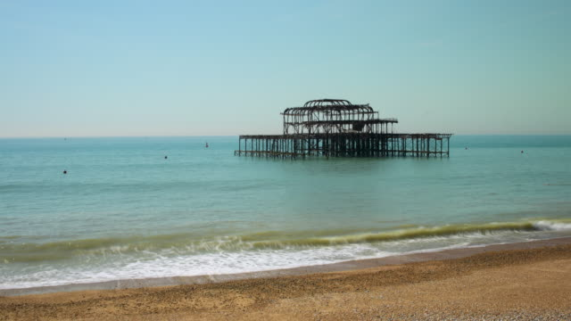 time lapse shot of waves rolling onto brighton beach near the derelict west pier. - buoy stock videos & royalty-free footage