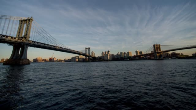 time lapse shots of both the manhattan bridge and the brooklyn bridge as boats and ferries pass by along the east river in new york ny - east river stock videos & royalty-free footage