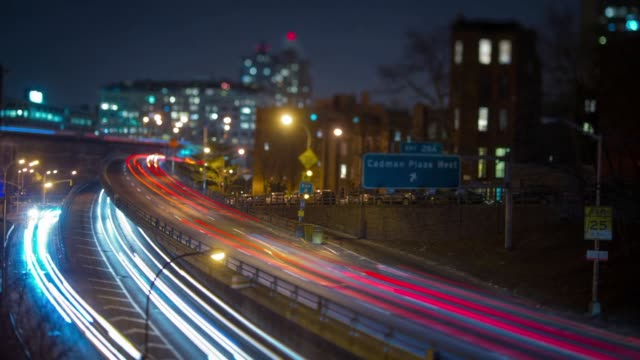 Time lapse shots of vehicle traffic moving on roads and highways in Brooklyn New York Red and blue streams of light line streets and highways on the...