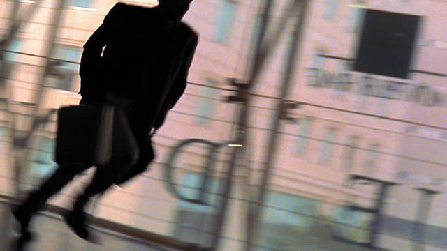 canted pan time lapse silhouette of man running down hallway carrying briefcases - in silhouette video stock e b–roll