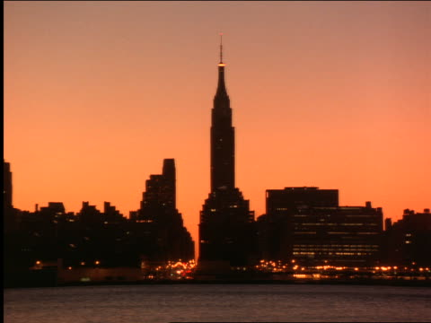 time lapse silhouette of nyc skyline with sun rising - 2001 stock-videos und b-roll-filmmaterial