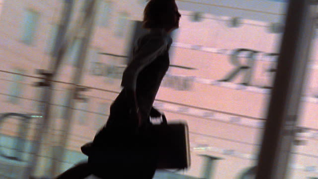 CANTED PAN time lapse silhouette of woman running down hallway carrying briefcases