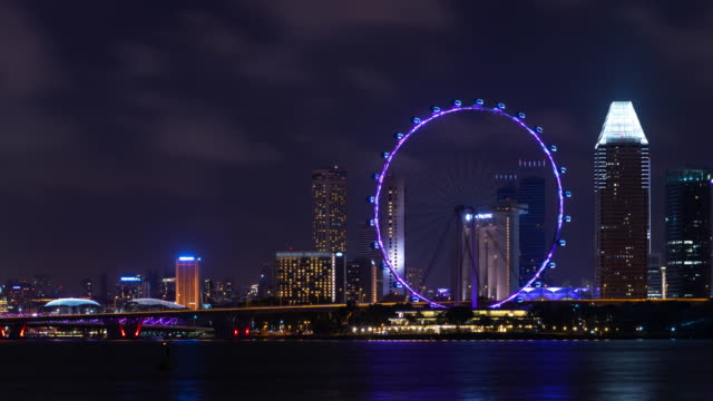 4k time lapse: singapore city skyline with illuminated skyscrapers and ferris wheel at night - big wheel stock videos & royalty-free footage