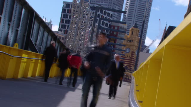 time lapse southgate foot bridge pedestrians crossing flinders street station clock tower in the background - footbridge stock videos & royalty-free footage