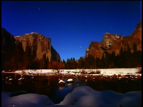 time lapse stars moving in sky above yosemite valley with el capitan day to dusk in winter / water in foreground / california - 1987 stock videos & royalty-free footage