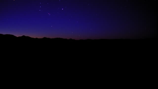 PAN time lapse stars rising over mountains / sky brightening to white / Aspen, Colorado