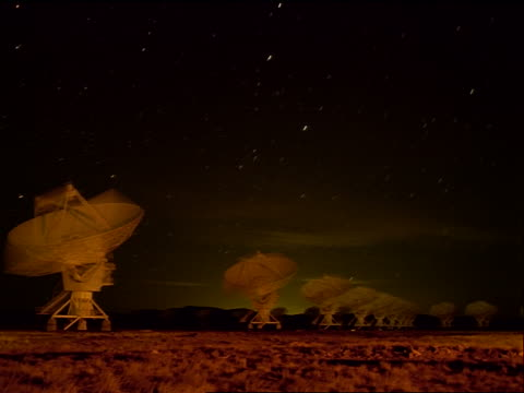 stockvideo's en b-roll-footage met time lapse starscape over moving vla radio telescope dishes at night / new mexico - astronomietelescoop