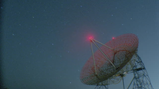 time lapse starscape over radar dish with red light on tip at night