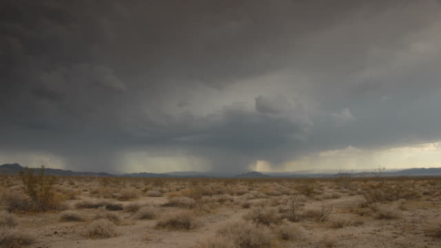 vidéos et rushes de time lapse storm clouds and lightning on a desert plain - aride