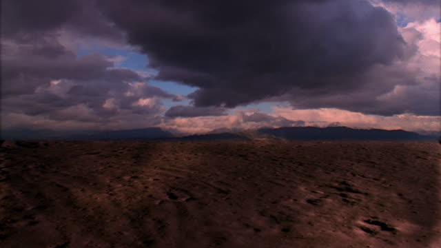 time lapse storm clouds clearing over cracked soil in desert - storm cloud stock videos & royalty-free footage
