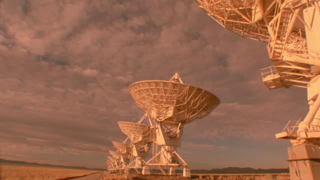 pan time lapse storm clouds over moving vla radio telescope dishes / new mexico - astronomiskt teleskop bildbanksvideor och videomaterial från bakom kulisserna