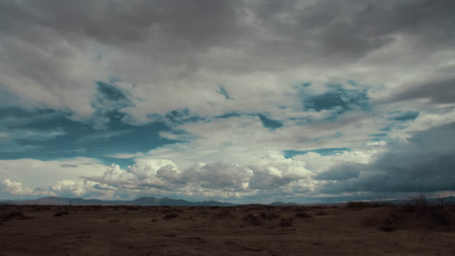 Time lapse storm clouds travel over a desert plain.