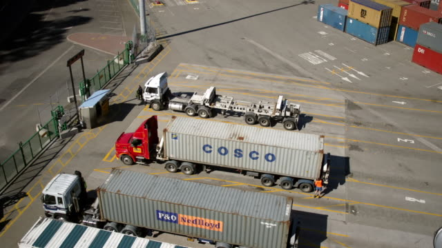 vídeos y material grabado en eventos de stock de time lapse straddle carriers loading cargo containers onto trucks in parking lot of commercial dock / port of lyttelton, new zealand - pórtico automotor