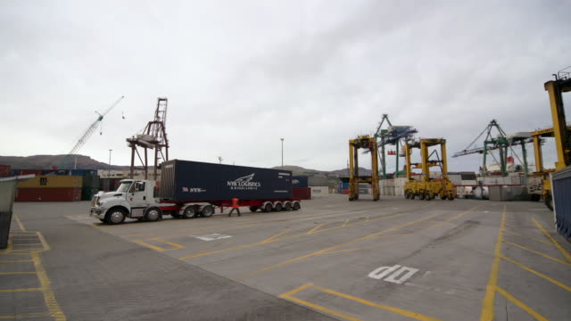 vídeos y material grabado en eventos de stock de time lapse straddle carriers loading cargo containers onto trucks in parking lot of port / port of lyttelton, new zealand - pórtico automotor