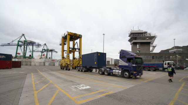 vídeos y material grabado en eventos de stock de time lapse straddle carriers loading cargo containers onto trucks in port / port of lyttelton, new zealand - pórtico automotor