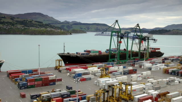 vídeos y material grabado en eventos de stock de time lapse straddle carriers moving cargo containers around container park and containers being unloaded from moored ship by cranes at port lyttelton / lyttelton, new zealand - pórtico automotor