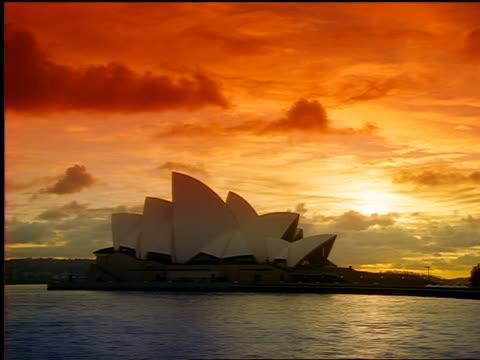 time lapse sun rising above harbor + sydney opera house / sydney, australia - bennelong point stock videos and b-roll footage