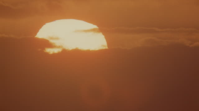Time lapse sun rising behind clouds