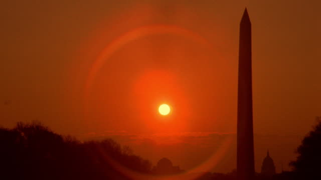 time lapse sun rising behind silhouette of washington monument / capitol building in background / washington d.c. - monument stock videos & royalty-free footage