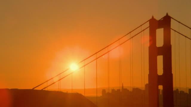 vídeos de stock e filmes b-roll de time lapse sun rising behind silhouetted golden gate bridge / some flare / san francisco, california - super exposto