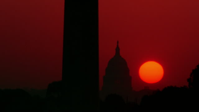 vídeos de stock e filmes b-roll de time lapse sun rising behind u.s. capitol building and washington monument / washington d.c. - capitol hill