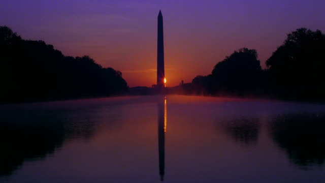 time lapse sun rising behind washington monument / reflection in reflecting pool in foreground / washington d.c. - reflecting pool washington dc stock videos & royalty-free footage