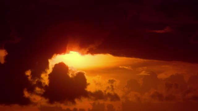 Time lapse sun setting behind clouds in orange sky