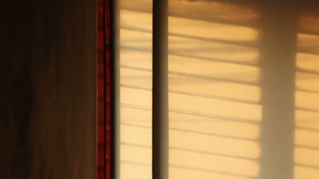 time lapse: sunlight shadows through the window shutters. - persiana caratteristica architettonica video stock e b–roll