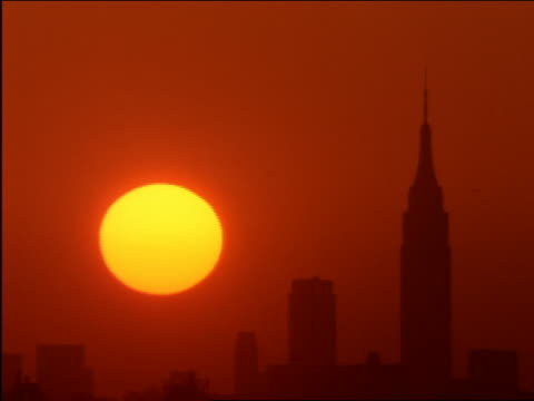 time lapse sunrise behind silhouette of Empire State Building