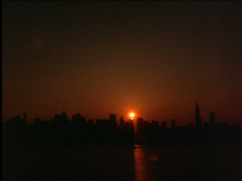time lapse sunrise + clouds over silhouette of nyc skyline with river in foreground - 1 minute or greater stock videos & royalty-free footage