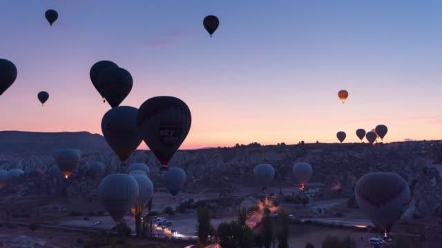 vídeos de stock, filmes e b-roll de lapso de tempo: nascer do sol colorido balão de ar quente vale da capadócia no parque nacional goreme, capadócia, turquia - capadócia