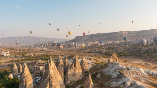 vídeos de stock, filmes e b-roll de lapso de tempo: sunrise hot air balloons voando sobre a paisagem rock goreme national park capadócia na turquia - arts culture and entertainment