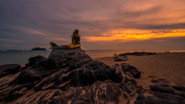 stockvideo's en b-roll-footage met timelapse sunrise scène van zeemeermin standbeeld, beroemde reis plaats in songkhla, thailand - rocking