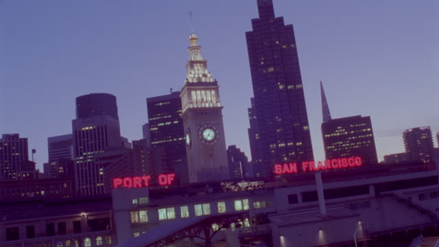 time lapse sunset behind port of san francisco buildings / day to night - baia di san francisco video stock e b–roll