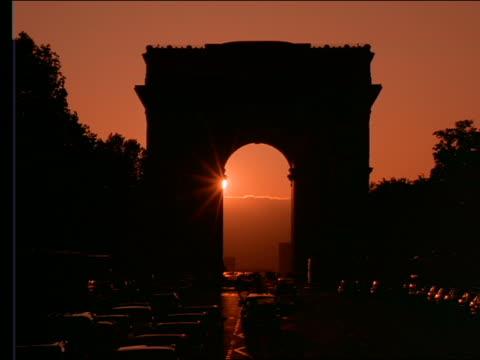 vidéos et rushes de time lapse sunset behind silhouette of arc de triomphe + traffic - arc élément architectural