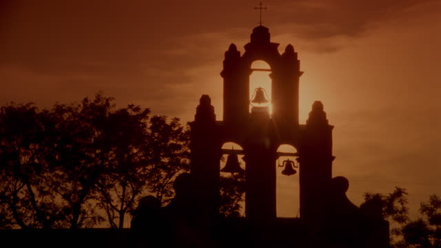 time lapse sunset behind silhouette of bells of mission san juan / san antonio, texas - tre oggetti video stock e b–roll
