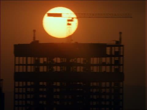 time lapse sunset behind silhouette of bldg under construction - romantische stimmung stock-videos und b-roll-filmmaterial