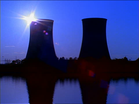 time lapse sunset behind silhouetted nuclear power plant / lake in foreground / Tennessee